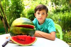 garçon avec la tranche de pastèque sur le fond de jardin d'été Photographie stock libre de droits