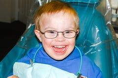 Garçon avec le Bas-syndrome se reposant dans le dentiste Chair Photographie stock libre de droits