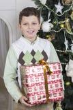 Garçon avec le cadeau énorme de Noël Photo stock