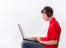 Garçon avec le casque et l'ordinateur portable Photographie stock libre de droits