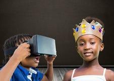 Garçon avec le casque et la fille de VR avec la couronne devant le tableau noir Photos stock