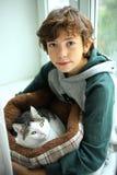 Garçon avec le chat dans la fin de lit d'animal familier vers le haut de la photo Photos stock