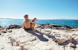 Garçon avec le chien de briquet se reposant ensemble sur la côte rocheuse à ensoleillé Photo libre de droits