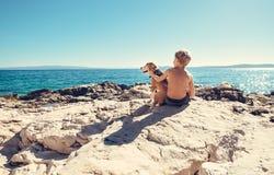 Garçon avec le chien de briquet se reposant ensemble sur la côte rocheuse à ensoleillé Image stock