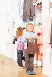 Garçon avec le gilet sur le cintre et la fille choisissant des vêtements Images libres de droits