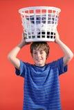 Garçon avec le panier de blanchisserie sur le hea Photo libre de droits