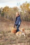 Garçon avec le plein panier des champignons avec le chien sur la clairière de forêt Photo stock