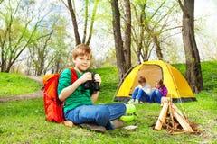 Garçon avec le sac à dos rouge et binoculaire heureux au camp Photos stock