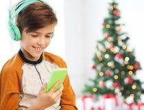 Garçon avec le smartphone et les écouteurs à Noël Photo libre de droits