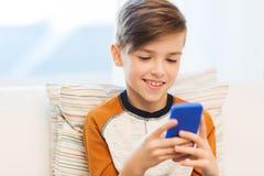 Garçon avec le smartphone textotant ou jouant à la maison Photographie stock