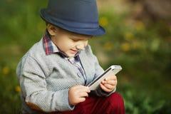 Garçon avec le téléphone se reposant sur l'herbe Photo libre de droits
