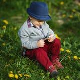 Garçon avec le téléphone se reposant sur l'herbe Images stock