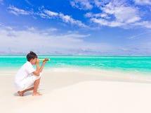 Garçon avec le télescope sur la plage Image stock