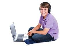 Garçon avec les écouteurs en fonction et l'ordinateur portatif d'isolement Photographie stock libre de droits