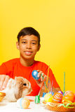 Garçon avec les oeufs de pâques et le lapin mignon sur la table Image stock