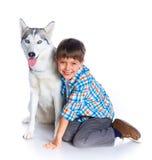 Garçon avec son chien de traîneau de chien Photo stock