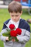 Garçon avec un bouquet des roses pour sa mère Photographie stock libre de droits