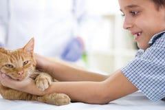 Garçon avec un chat à la maison Photographie stock libre de droits