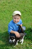 Garçon avec un chaton sur une herbe verte Image stock