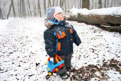 Garçon avec un jouet dans une forêt neigeuse Photographie stock libre de droits