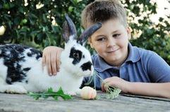 Garçon avec un lapin dans le jardin Photos stock