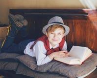 Garçon avec un livre sur le banc image libre de droits