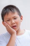 Garçon avec un mal de dents photos stock