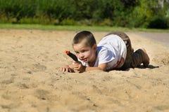 Garçon avec une arme à feu sur le terrain de jeu Image libre de droits