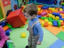 Garçon ayant l'amusement au parc d'attractions d'enfants et au centre d'intérieur de jeu Enfant jouant avec les jouets colorés da Photographie stock