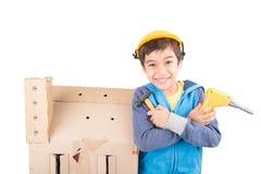 Garçon ayant l'amusement construisant une maison de poupée de papier Image libre de droits