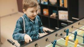 Garçon ayant l'amusement jouant le football de table banque de vidéos