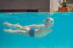 Garçon ayant l'amusement jouant sous l'eau dans la piscine des vacances d'été images libres de droits