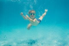 Garçon ayant l'amusement jouant sous l'eau dans la piscine des vacances d'été photos libres de droits