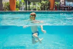 Garçon ayant l'amusement jouant sous l'eau dans la piscine des vacances d'été image stock