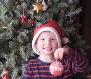 Garçon ayant la boule et le sourire de Noël Photographie stock libre de droits