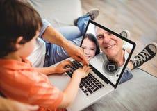 Garçon ayant un appel visuel avec le grand-père sur l'ordinateur portable photo libre de droits