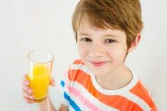 Garçon ayant un verre de jus de fruit régénérateur images stock