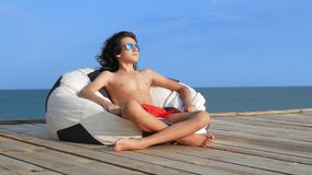 Garçon beau d'adolescent avec les cheveux bouclés dans des lunettes de soleil se reposant dans une chaise de sac sur une terrasse banque de vidéos