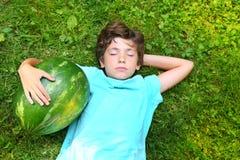 Garçon beau de la préadolescence avec la pastèque Photos stock