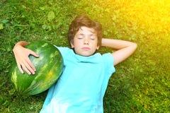 Garçon beau de la préadolescence riant avec la pastèque Image stock