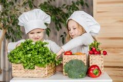 Garçon beau et belle jeune fille jouant dans les chefs de cuisine Nourriture saine légumes Image stock