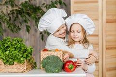 Garçon beau et belle jeune fille jouant dans les chefs de cuisine Nourriture saine légumes Image libre de droits