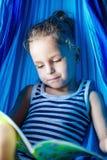 Garçon beau lisant un livre dans un hamac images stock