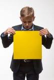 Garçon blond émotif d'adolescent dans un costume avec une feuille de papier jaune pour des notes Images stock