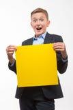 Garçon blond émotif d'adolescent dans un costume avec une feuille de papier jaune pour des notes Photographie stock