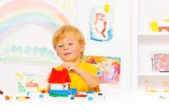 Garçon blond beau jouant avec les blocs en plastique Images stock