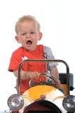 Garçon blond conduisant un véhicule de jouet Photographie stock