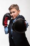 Garçon blond d'adolescent émotif dans un costume avec des gants de boxe dans des mains Photos libres de droits