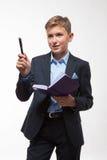 Garçon blond d'adolescent émotif dans un costume avec un journal intime et un stylo à disposition Image libre de droits