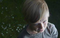 Garçon blond d'enfant en bas âge triste et pleurant dans le jardin en été Photos libres de droits